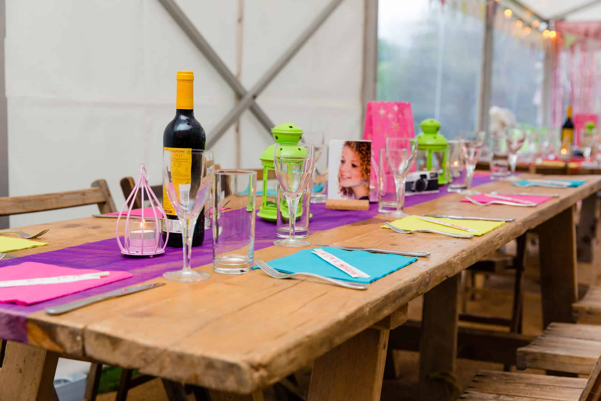 Colour table setting on rustic tables within a marquee