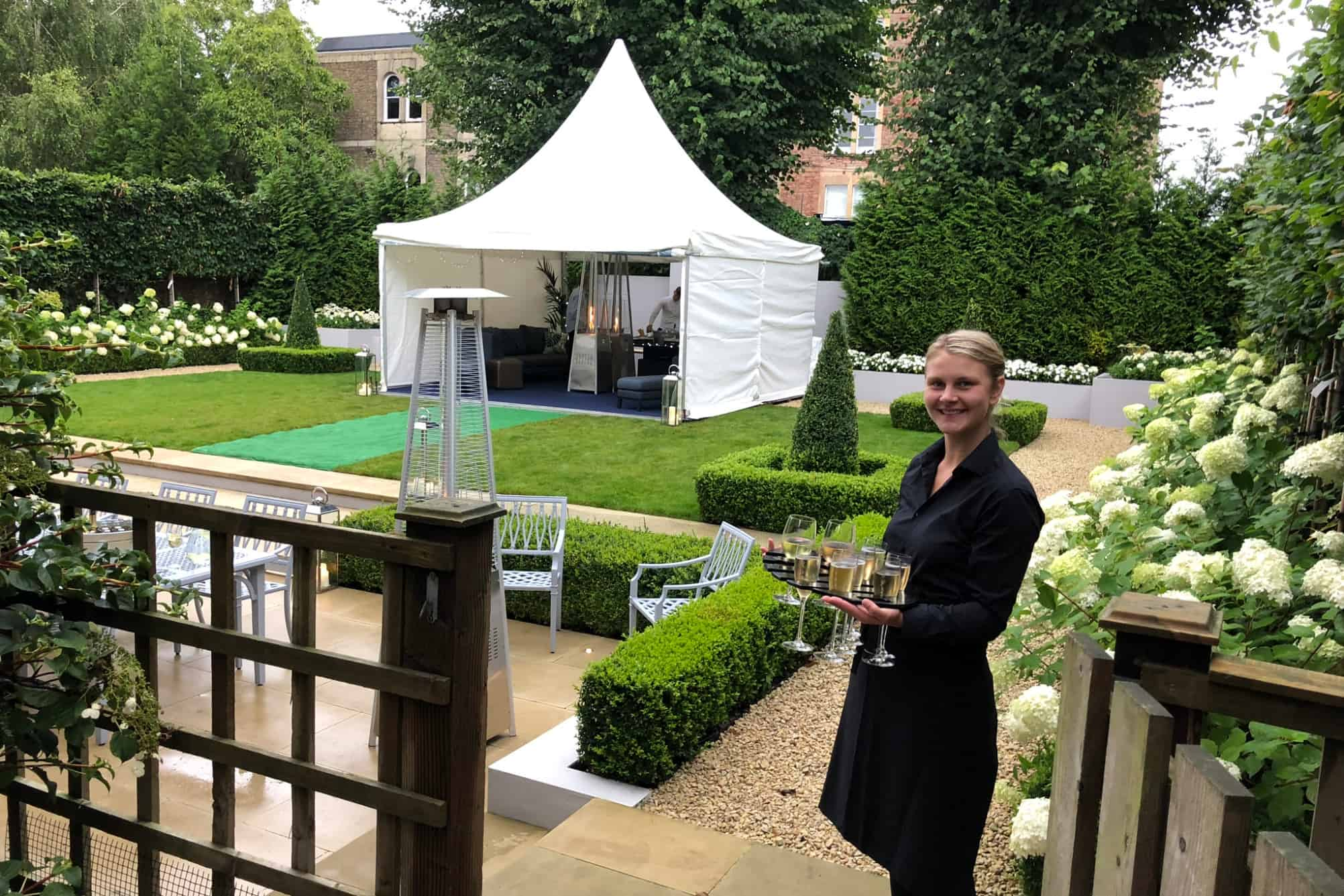 Event staff serving champagne in front of a Chinese hat marquee