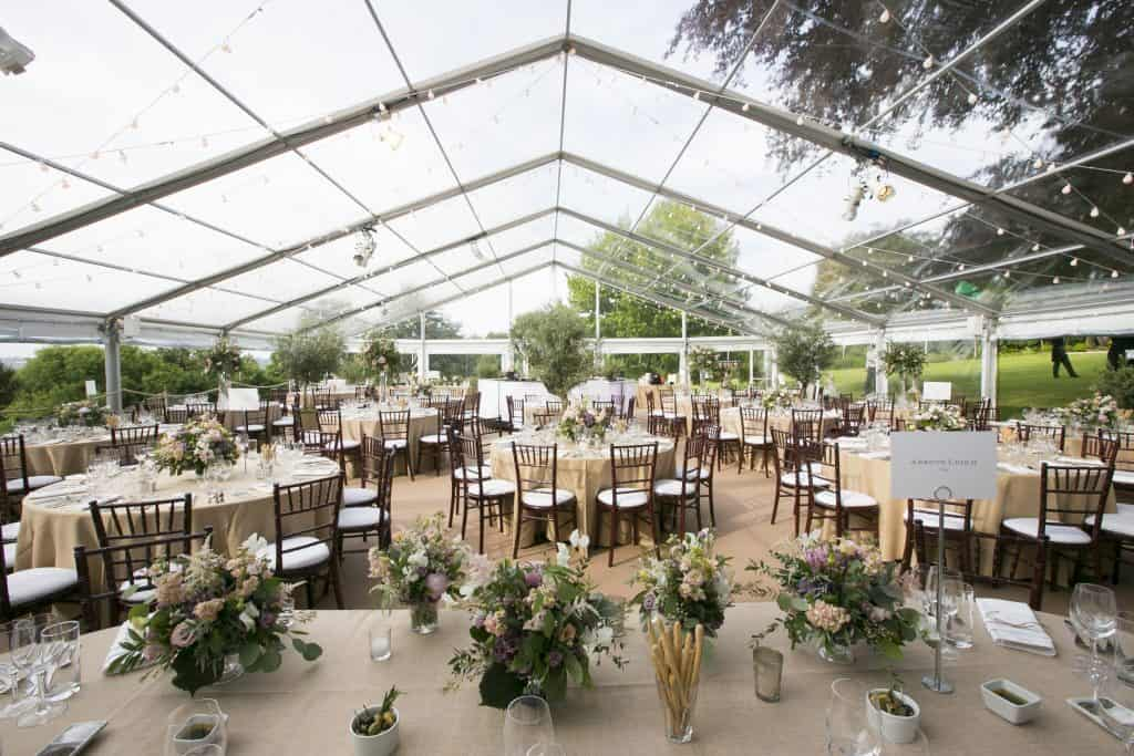 Clear roofed and walled wedding marquee in a countrside setting filled with beautifully dressed tables covered in flowers